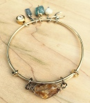 Gold plated 8 inch expandable bangle with wire wrapped citrine and an assortment of charms (blue kyanite, pearl, wishbone, rhinestone, 'bff eva'. $135