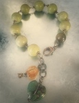 Mellow yellow/greenish smooth serpentine stone rounds (appr .5 inch in dia.) with wire wrapped citrine plus turquoise heart accents and a tiny brass flower bud...and large sterling silver clasp. Fits 6-7 inch wrist. $125